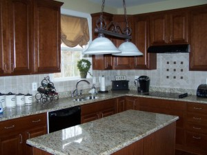 After - new granite - St. Cecilia; new backsplash; stained kitchen cabinets; new light fixture; new sink and faucet.